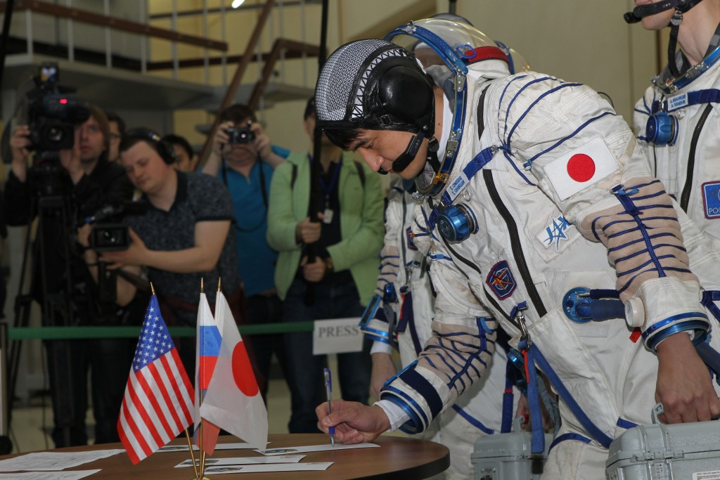 At the Gagarin Cosmonaut Training Center in Star City, Russia and suited in his Sokol launch and entry suit, Expedition 48-49 prime crewmember Takuya Onishi of the Japan Aerospace Exploration Agency signs in May 27 for his final Soyuz qualification exam. Onishi, Kate Rubins of NASA and Anatoly Ivanishin of Roscosmos will launch June 24 on the Soyuz MS-01 spacecraft from the Baikonur Cosmodrome in Kazakhstan for a four-month mission on the International Space Station. NASA/Stephanie Stoll